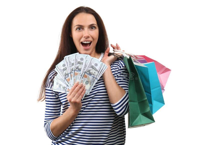Возбужденная молодая женщина с хозяйственными сумками и серией денег на белой предпосылке стоковая фотография rf