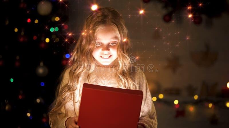 Возбужденная подарочная коробка отверстия девушки, представляет для ребенка в детском доме, чуде рождества стоковая фотография