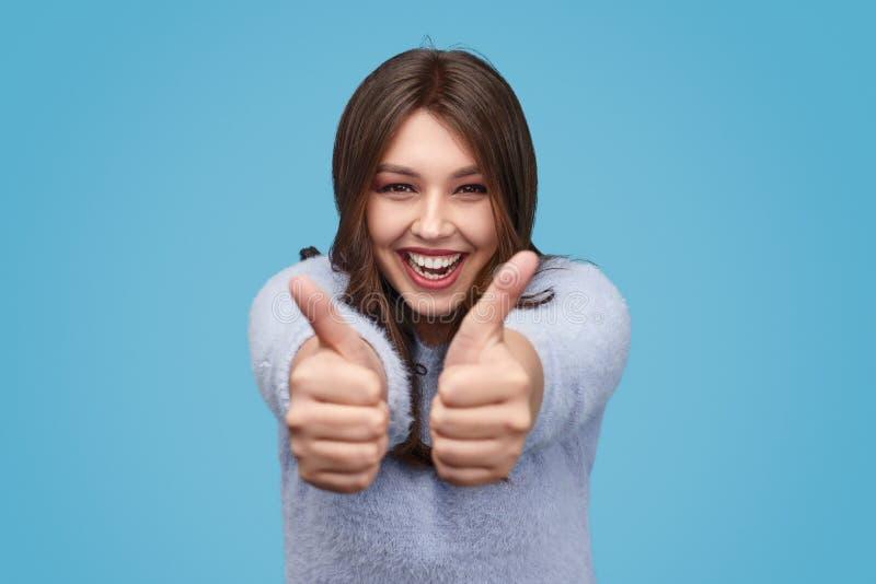 Возбужденная полная женщина показывая жестами большие пальцы руки вверх стоковая фотография