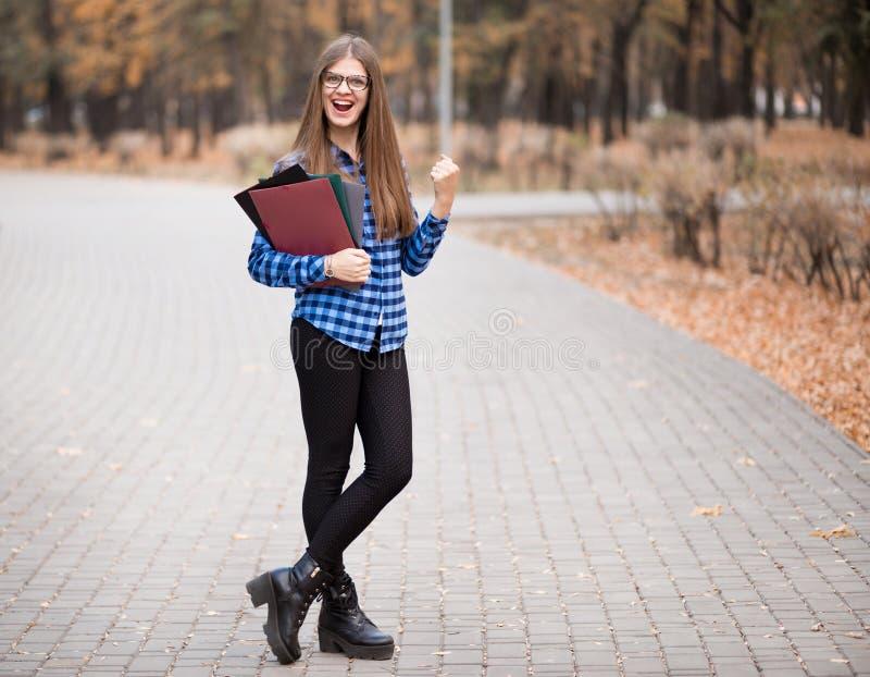 Возбужденная студентка чувствует эйфоричной празднующ онлайн результат достижения успеха выигрыша, молодую женщину счастливую о х стоковое фото
