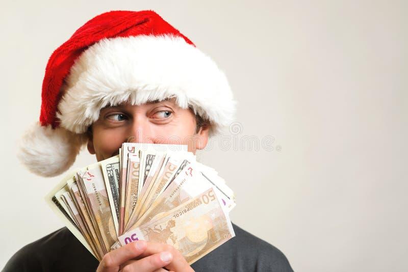 Возбужденная удивленная шляпа рождества человека нося держа деньги Принципиальная схема рождества Счастливый человек задерживая м стоковые изображения rf