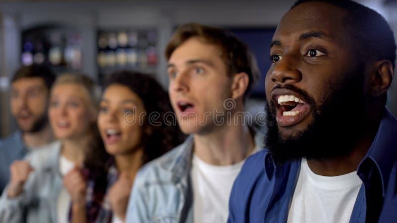 Возбужденные вентиляторы слушая объявление победителя конкуренции, торжество, успех стоковая фотография