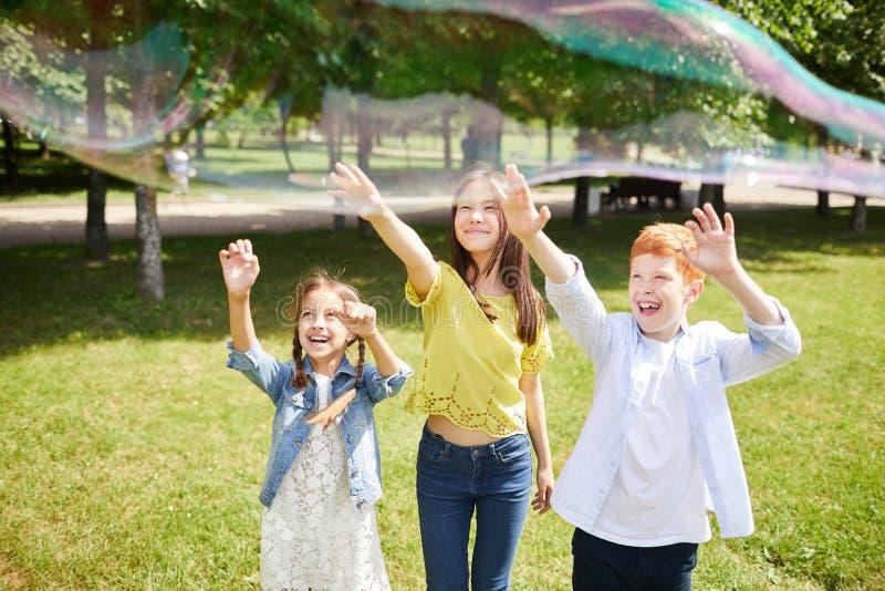Возбужденные дети достигая руки к пузырю мыла стоковое изображение rf