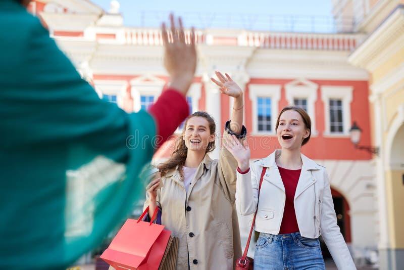 Возбужденные друзья встречая на улице стоковые фотографии rf