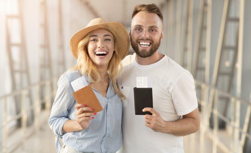 Возбужденные пары идя на каникулы и держа паспорта стоковое изображение