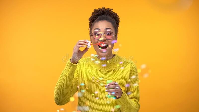 Возбужденные пузыри мыла молодой женщины дуя, ребяческое настроение,  стоковое изображение rf