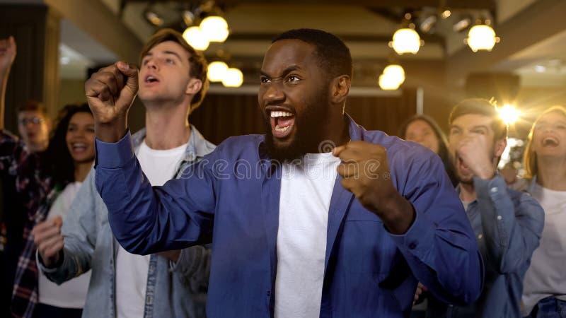 Возбужденный Афро-американский человек с победой ликования друзей, успехом проекта стоковая фотография rf