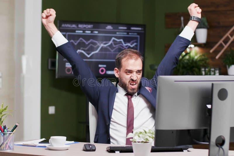 Возбужденный бизнесмен счастливо поднимая его руки в воздухе стоковая фотография rf