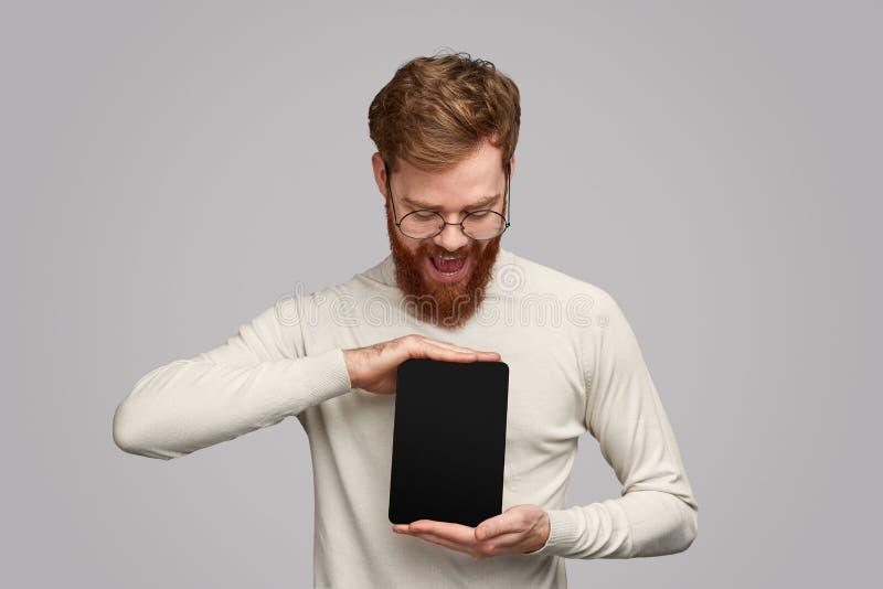 Возбужденный бородатый человек представляя приложение на планшете стоковые изображения