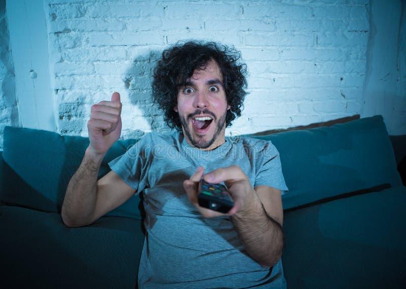 Возбужденный молодой человек вентилятора спорт смотря футбольный матч на телевидении, празднующ цель и кричащий стоковое изображение rf