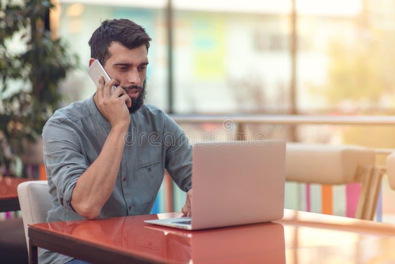 Возбужденный счастливый бородатый фрилансер читая электронную почту с результатами о победе в современном онлайн состязании сидя  стоковая фотография rf