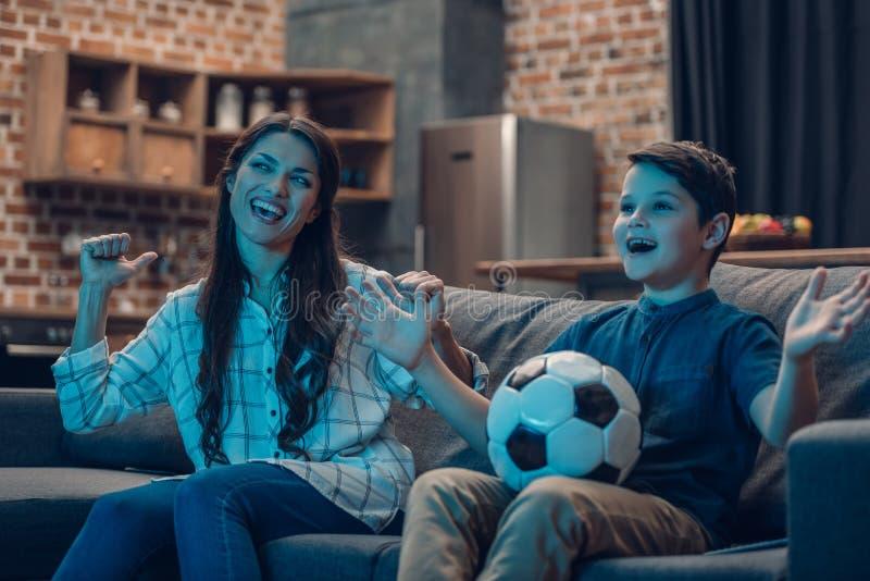 Возбужденный футбол матери и сына наблюдая стоковое фото