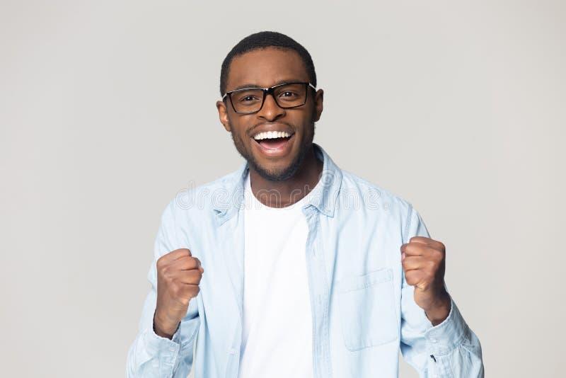 Возбужденный черный мужчина в стеклах чувствует осчастливленным с новостями стоковые изображения rf