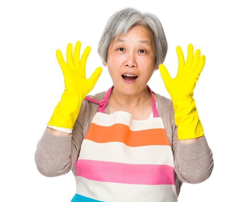 Возбудите домохозяйку с пластичными перчатками и поднимите руку вверх стоковые изображения