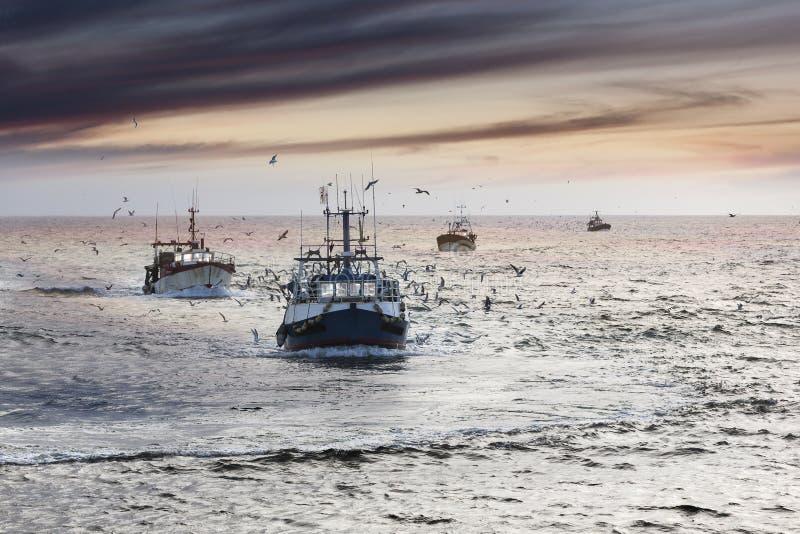 Возвращение домой: Утомленные корабли fishermans причаливая после тяжелого дня стоковые фотографии rf