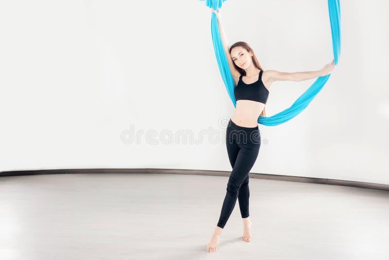 Воздушная йога мухы в белом спортзале Молодые красивые женщины практикуя протягивающ pilates в голубом гамаке стоковое фото