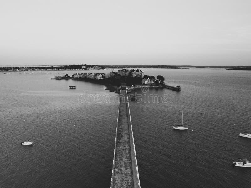 Воздушная съемка моста и маленький заселенный остров в море стоковое изображение