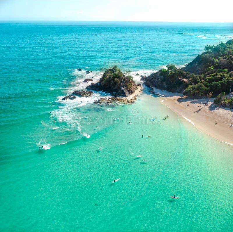 Воздушная съемка на восходе солнца над океаном и пляжем с белым песком с пловцами и серферами наслаждаясь летом стоковое изображение rf