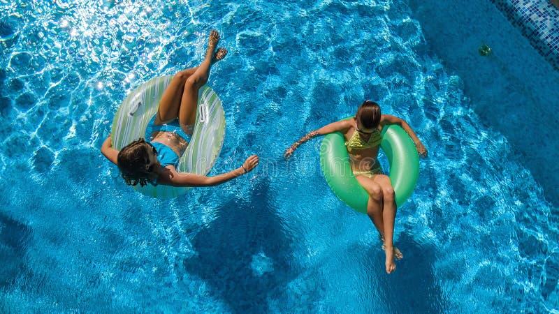 Воздушное взгляд сверху детей в бассейне сверху, счастливые дети плавает на раздувных donuts кольца и имеет потеху в воде стоковая фотография