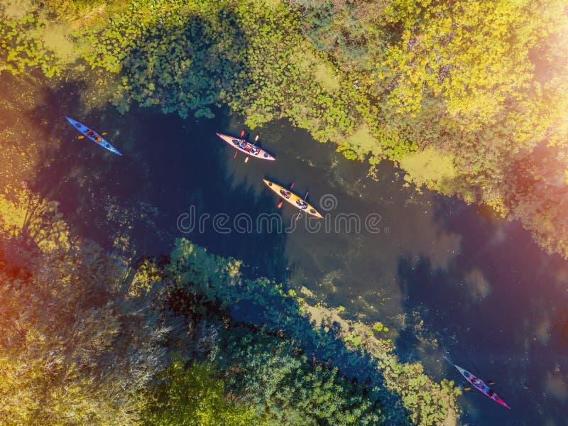 Воздушное фото взгляда глаза птицы трутня счастливой семьи с 2 детьми наслаждаясь ездой каяка на красивом реке Мальчик и стоковое фото