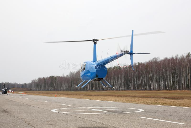 Воздушные судн - голубой малый вертолет делает полет на низком заде высоты стоковая фотография