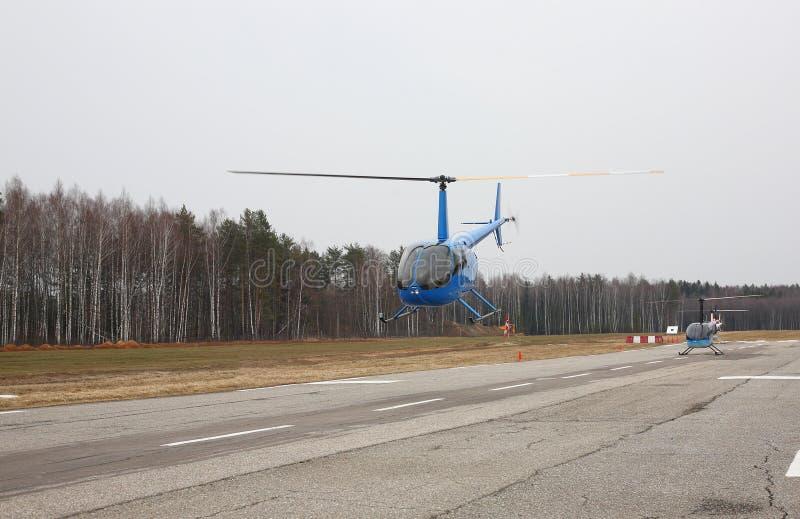 Воздушные судн - голубой малый вертолет делает полет на низком fron высоты стоковая фотография rf