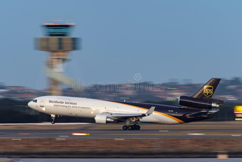 Воздушные судн груза UPS McDonnell Douglas MD-11F United Parcel Service принимая от аэропорта Сиднея сразу после захода солнца стоковые фото
