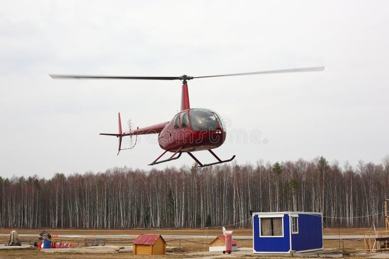 Воздушные судн - красный малый вертолет делает полет на низкой высоте стоковое изображение