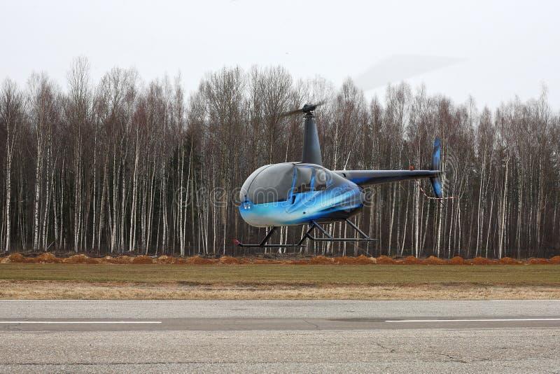 Воздушные судн - полет вертолета бирюзы малый на низкую высоту стоковое фото rf