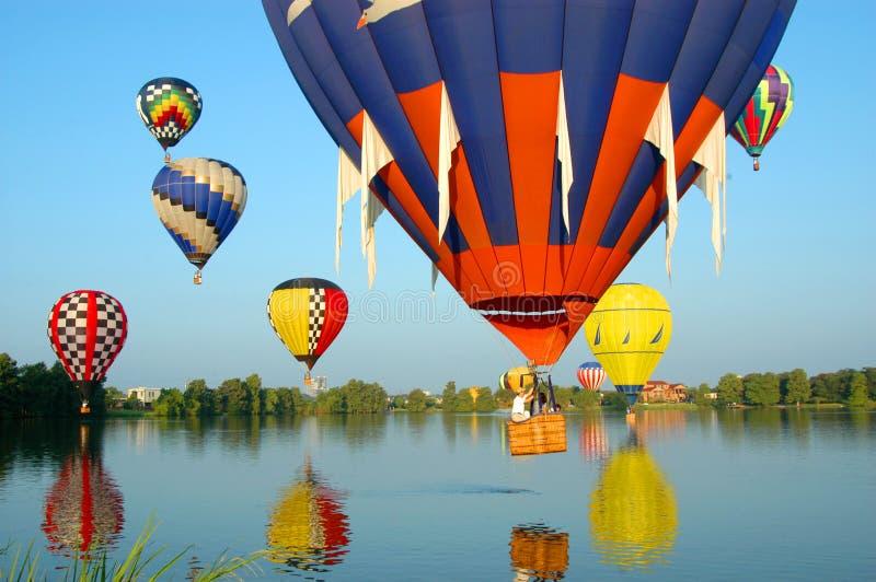 воздушные шары плавая над водой стоковое изображение