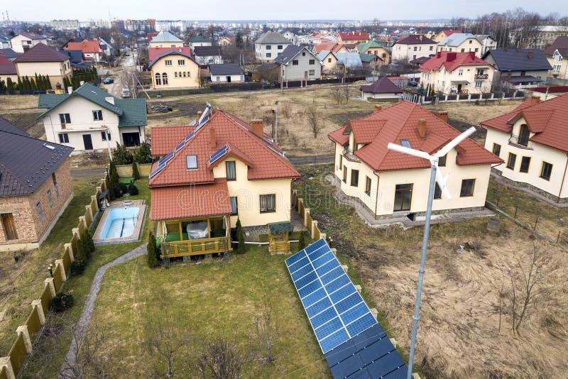 Воздушный взгляд сверху жилого района с новыми домами с панелями солнечного фото крыши voltaic, мельницей ветротурбины и отдельно стоковые изображения rf
