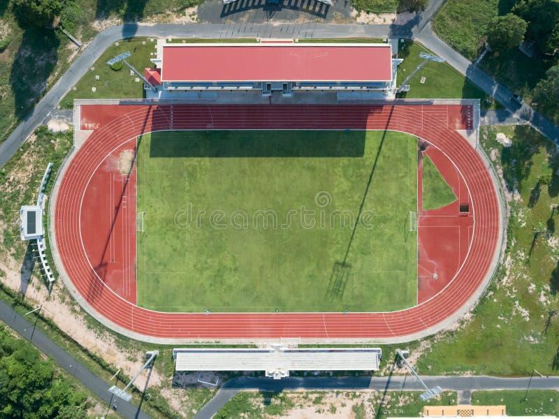 Воздушный взгляд сверху на футбольном поле, трибуна, футбольное поле с красным идущим следом трасса в стадионе стоковые изображения rf