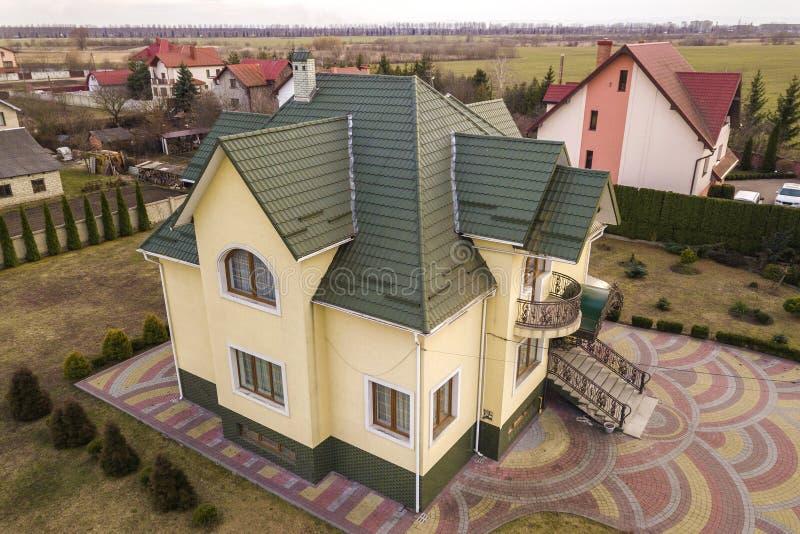 Воздушный взгляд сверху нового жилого коттеджа дома с крышей гонта на ограженном большом дворе на солнечный день стоковые изображения
