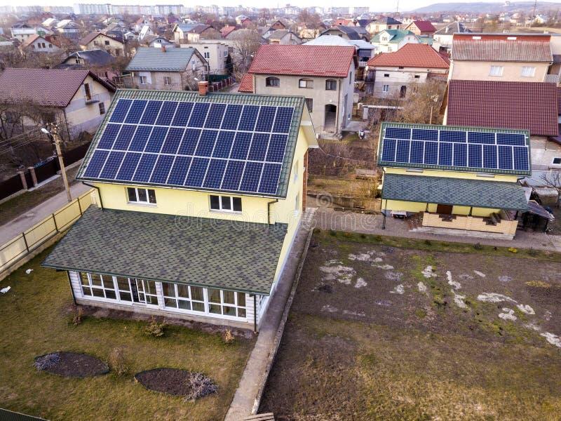 Воздушный взгляд сверху нового современного жилого коттеджа дома с системой панелей голубого сияющего солнечного фото voltaic на  стоковое фото rf