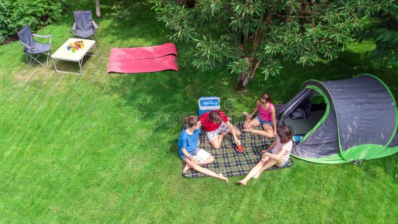Воздушный взгляд сверху семьи в месте для лагеря сверху, родители и дети ослабляют и имеют потеху в парке, шатре и располагаясь л стоковые фото