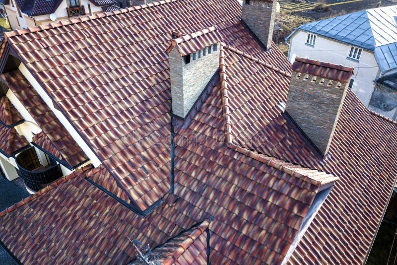 Воздушный взгляд сверху сложной крыши гонта металла дома и высоких каминов кирпича Толь, конструкция, ремонт и ремонтные работы стоковые изображения rf