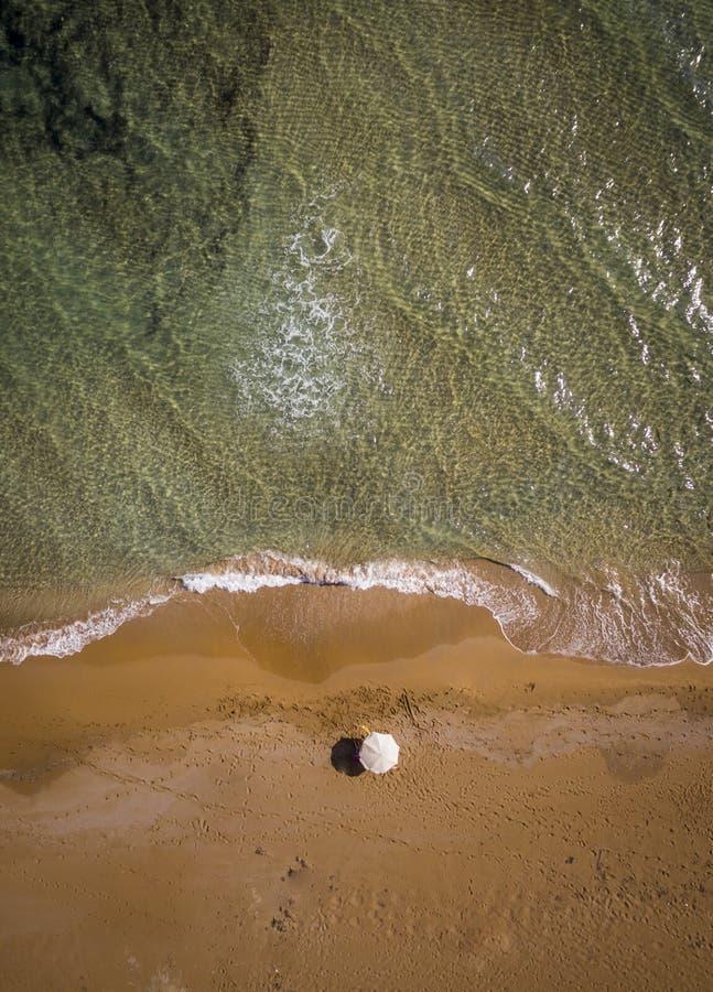 Воздушный взгляд трутня уединенного пляжа и одного зонтика, кристально ясных вод Корфу Греция стоковое изображение