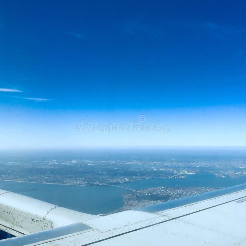 Воздушный выстрел ландшафта из окна самолета с океаном и высокими зданиями под голубым небом стоковые фото