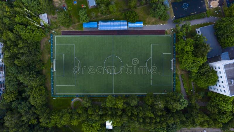 Воздушный городской взгляд футбольного поля с игроками стоковое фото