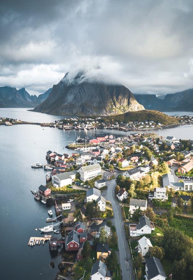 Воздушный панорамный вид трутня рыбацкого поселка Reine традиционного в архипелаге Lofoten в северной Норвегии с синью стоковые фото