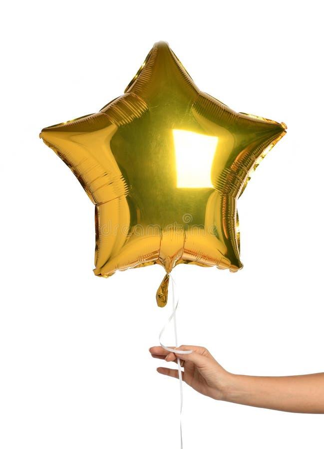 Воздушный шар звезды золота владением руки женщины для торжества вечеринки по случаю дня рождения изолированный на белизне стоковое изображение rf