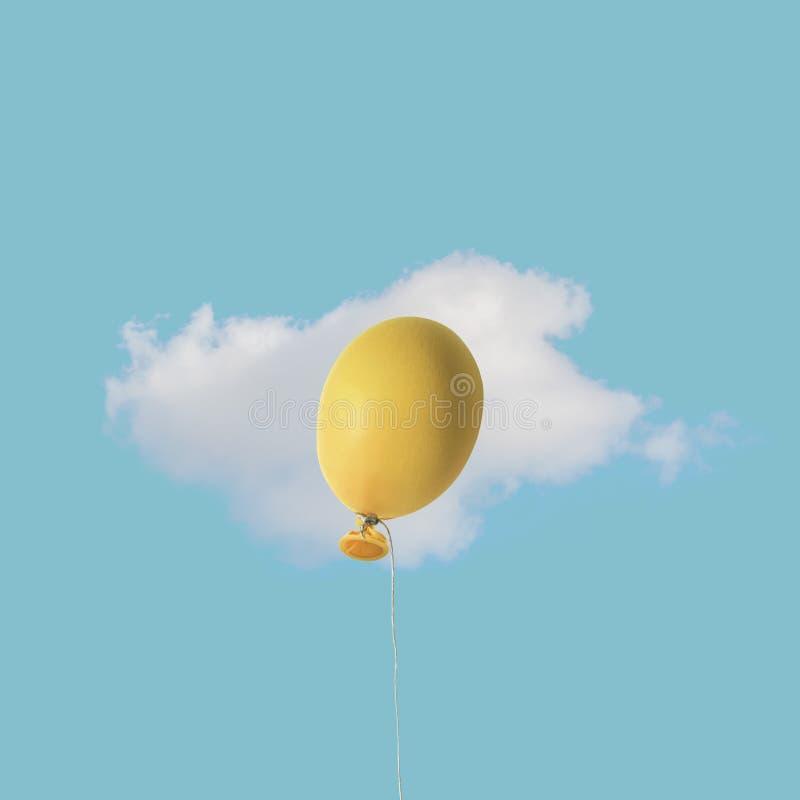 Воздушный шар яйца пасхи желтый с белым облаком на голубом небе Концепция еды минимальная стоковое изображение