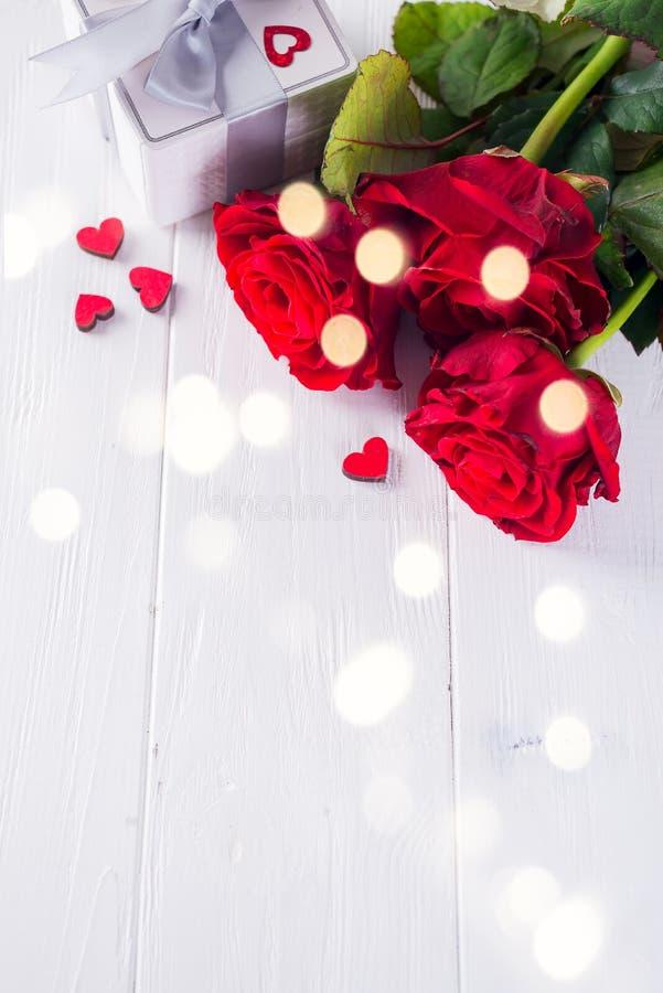 Возлюбленный Шоколад-любов Валентайн сформированный с подарочной коробкой на белой деревянной предпосылке с красными розами стоковое фото rf