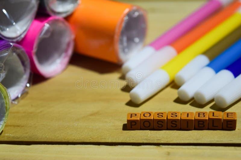 Возможный на деревянных кубах с красочными бумагой и ручкой, воодушевленностью концепции на деревянной предпосылке стоковое изображение