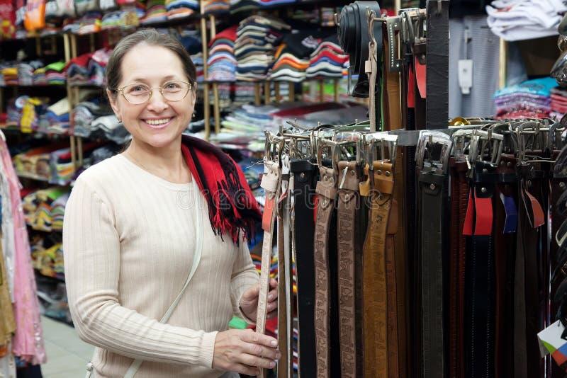 Возмужалая женщина выбирает кожаный пояс стоковые изображения rf