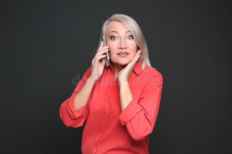 Возмужалая женщина говоря на мобильном телефоне стоковое фото