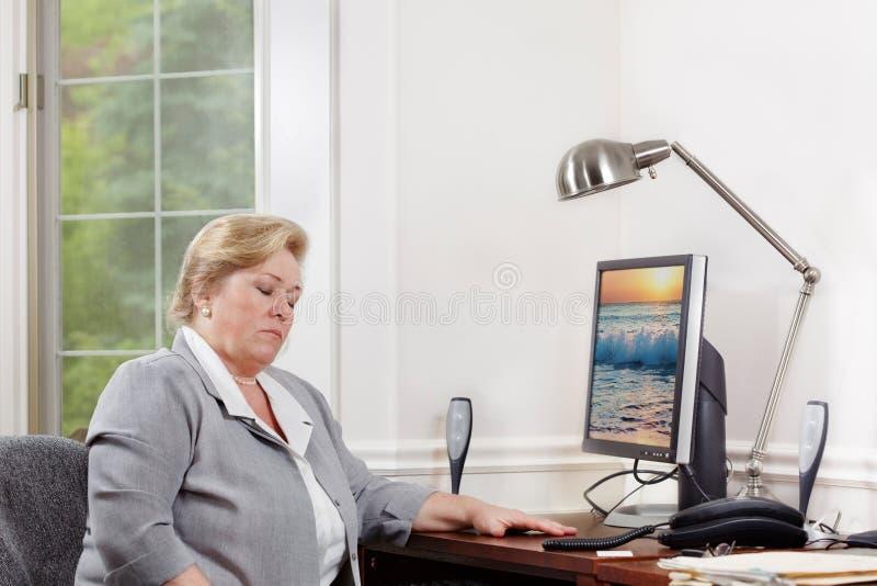 Возмужалая женщина дремая на столе стоковое изображение