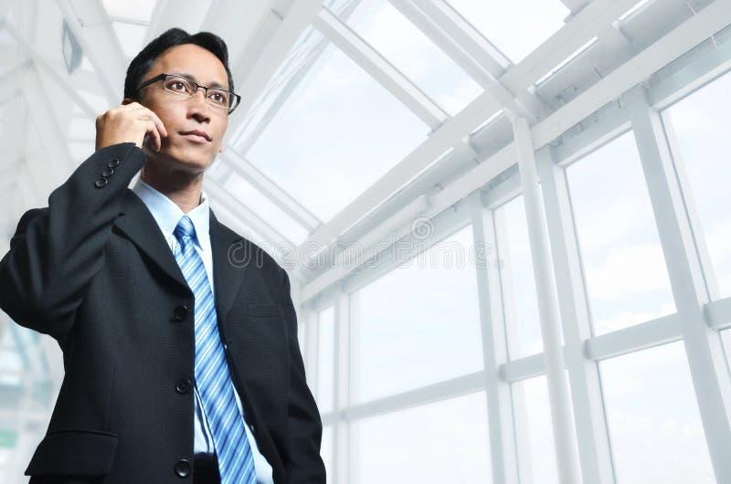 Возмужалый азиатский бизнесмен на телефоне стоковое изображение rf