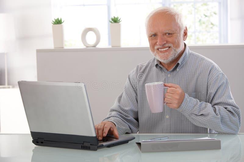 Возмужалый человек с усмехаться компьютера
