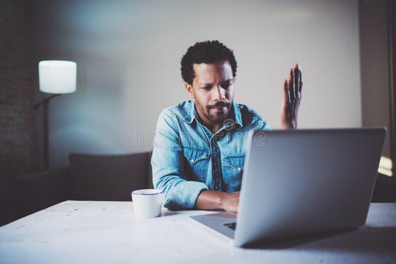 Возмутительный бородатый африканский человек делая видео- переговор через компьтер-книжку с партнерами пока работающ на coworking стоковое изображение rf